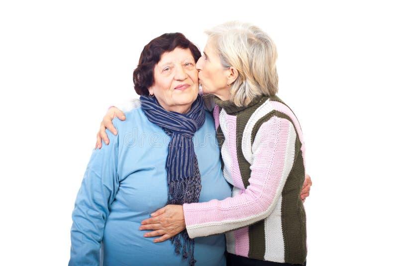 Senior daughter kissing elderly mother stock image
