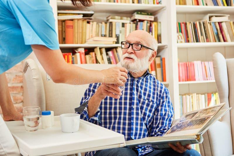 Senior with photo album gets medication royalty free stock image