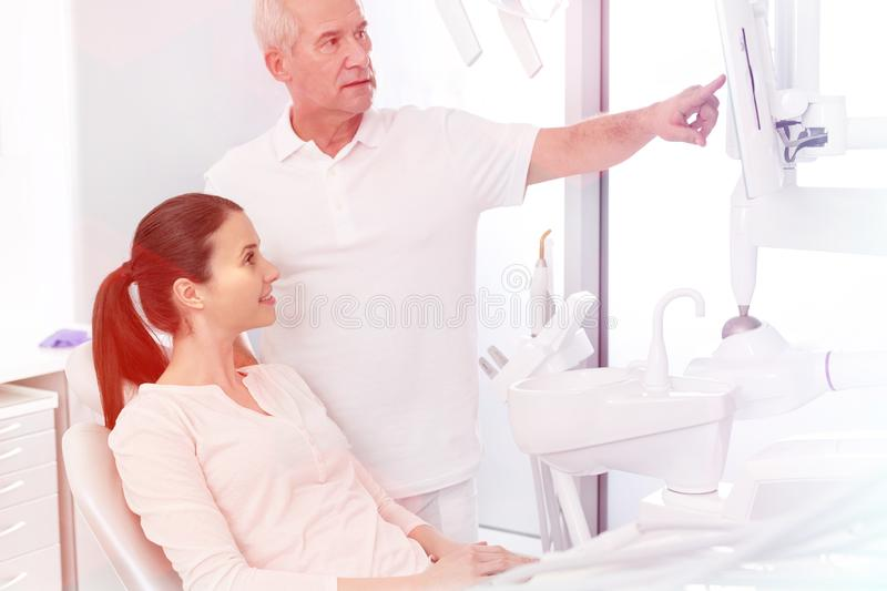 Senior dentist showing screen to patient at dental clinic stock photography