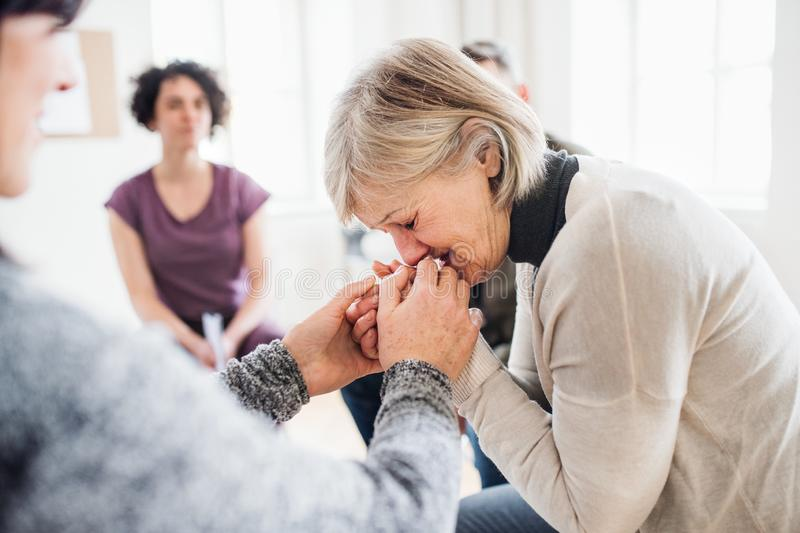 A senior depressed woman crying during group therapy. stock image