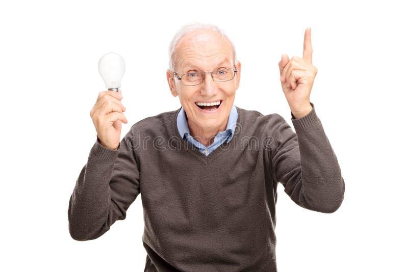 Senior, der eine Glühlampe hält und mit der Hand gestikuliert lizenzfreie stockfotos