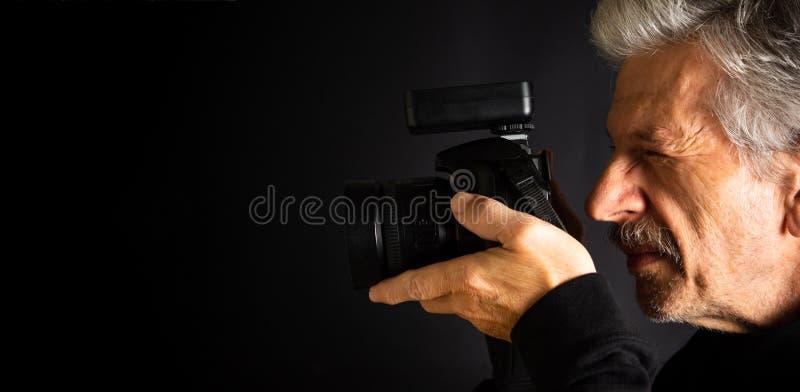 Senior, der einen Kameraabschluß aufbraucht stockfotografie