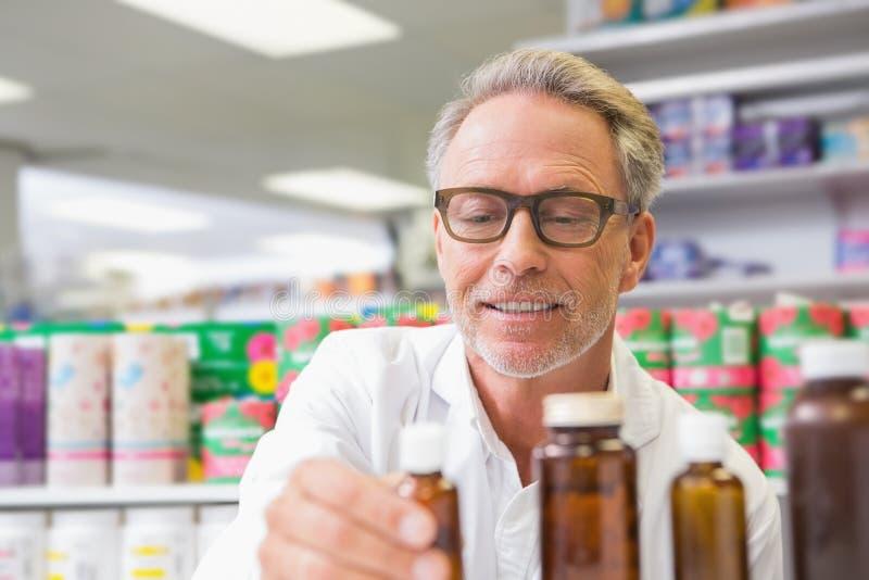 Senior, der Glas Medizin hält und betrachtet lizenzfreie stockfotos
