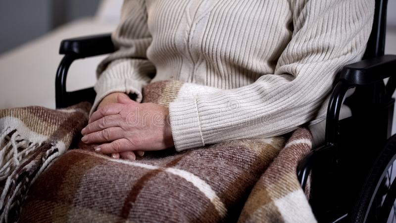 Senior disabled woman covered with blanket closeup, nursing home, retirement stock photo