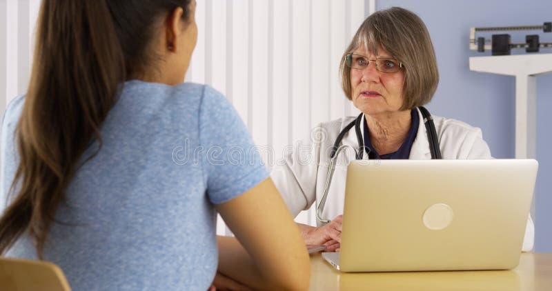 Senior doctor advising Hispanic woman patient royalty free stock image