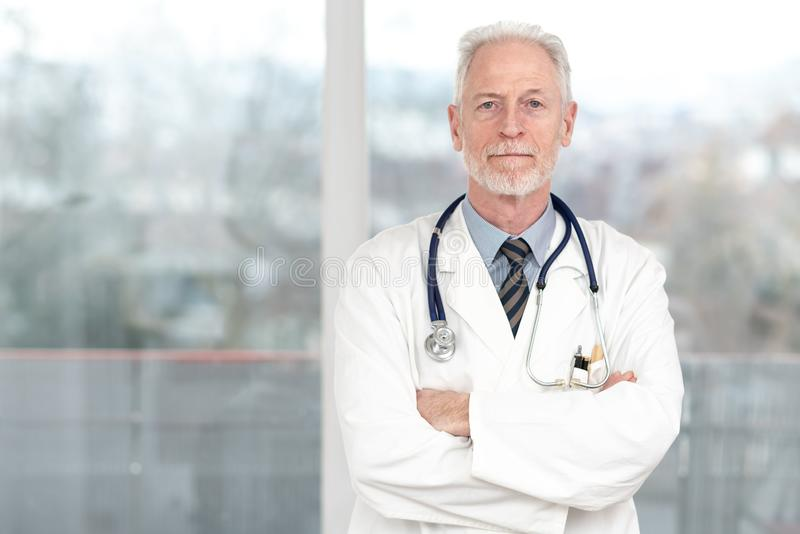Senior doctor with arms crossed royalty free stock photography