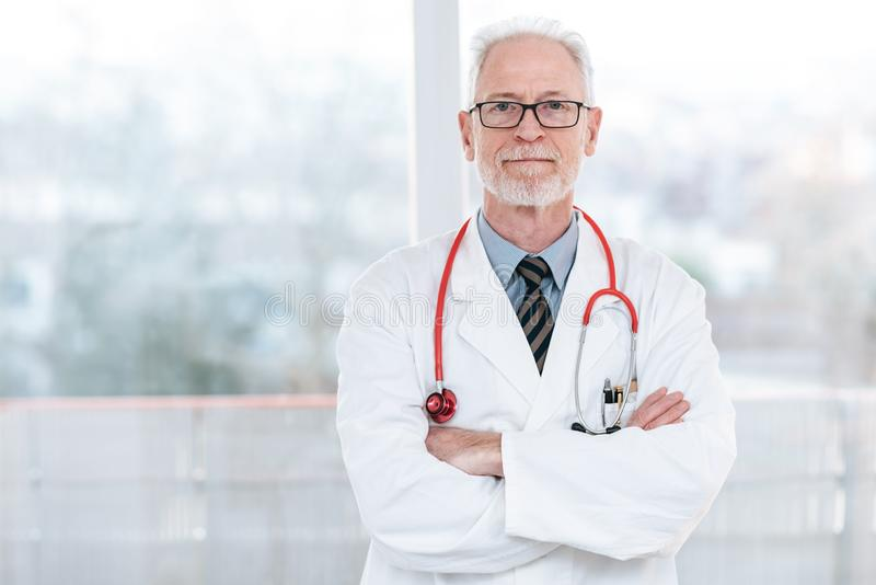 Senior doctor with arms crossed stock image