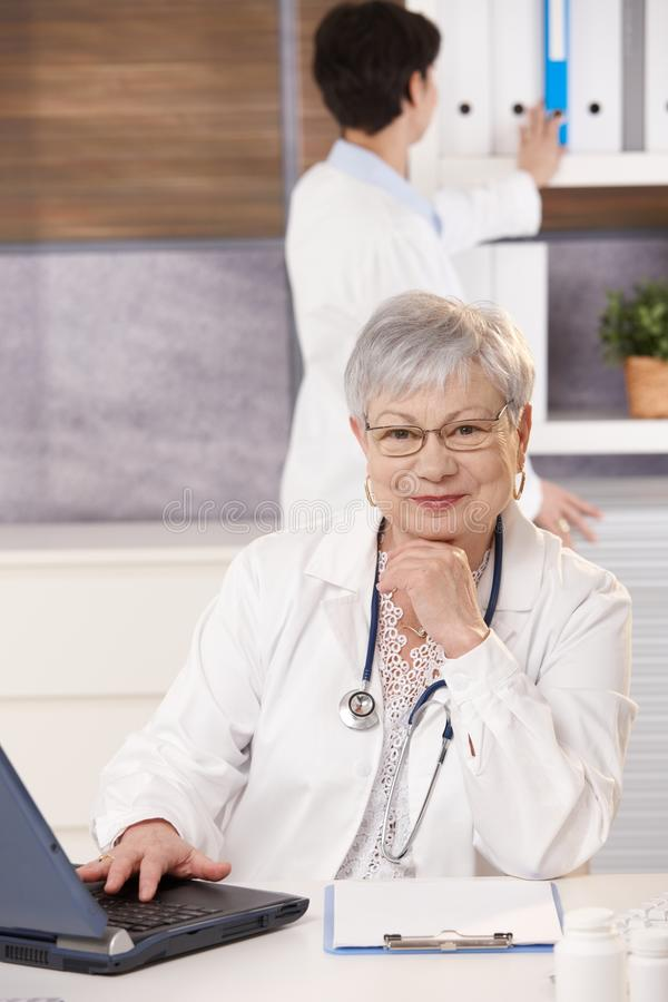 Senior Doctor And Assistant In Office Royalty Free Stock Images