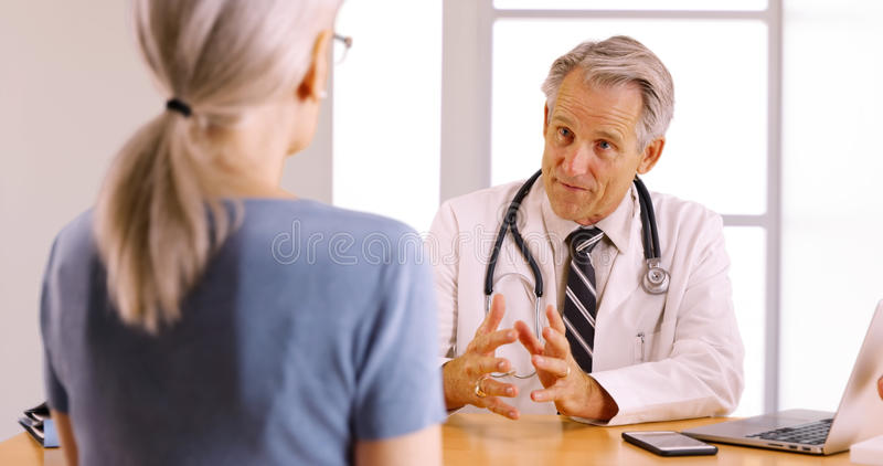Senior doctor discussing surgery procedure with elderly woman patient stock photography