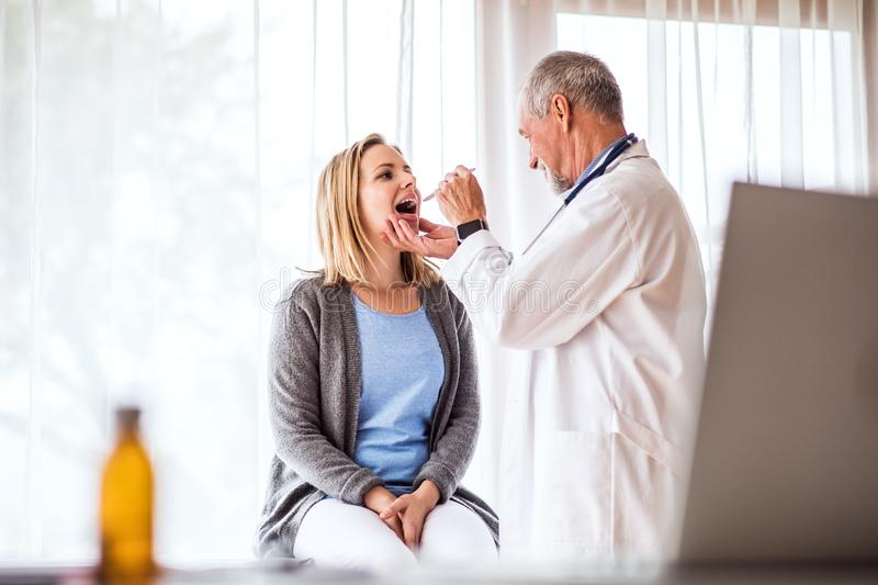 Senior doctor examining a young woman in office. Senior doctor examining a young woman. A doctor and a patient at the doctors office royalty free stock image