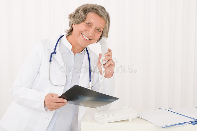 Senior doctor female hold x-ray and phone royalty free stock photos