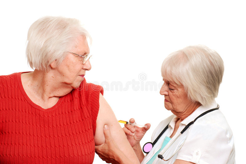 Senior doctor giving injection to elderly patient stock images