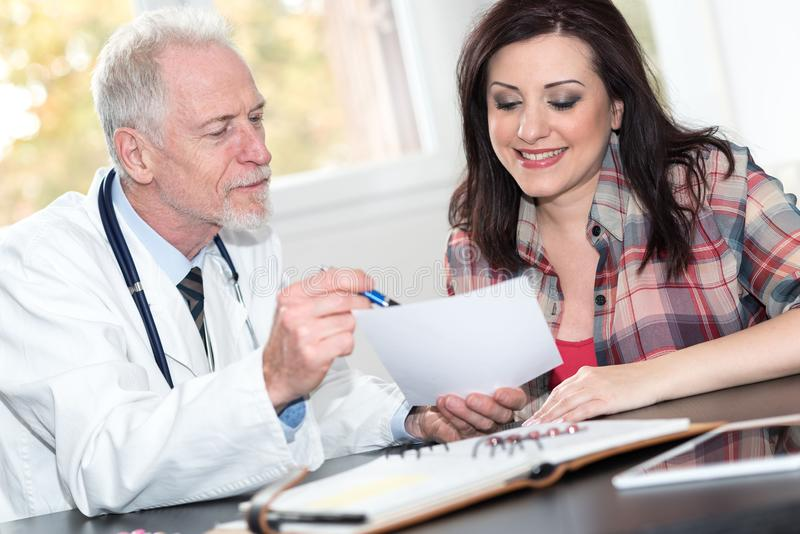 Senior doctor giving prescription to female patient royalty free stock photo