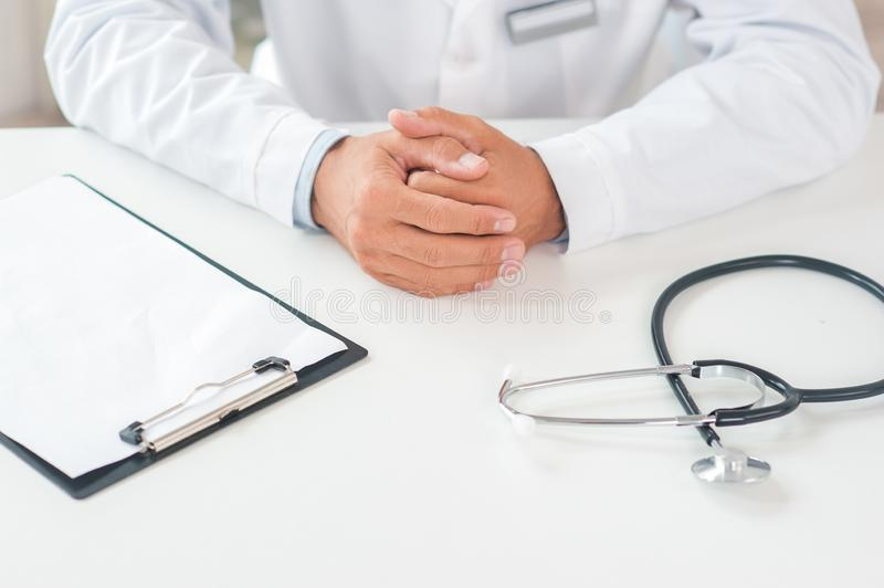 Senior doctor at his office in hospital working close-up sitting still top view stock photo