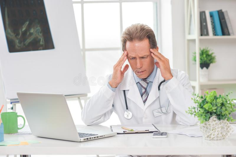 Senior doctor at his office in hospital working using laptop headache royalty free stock photo