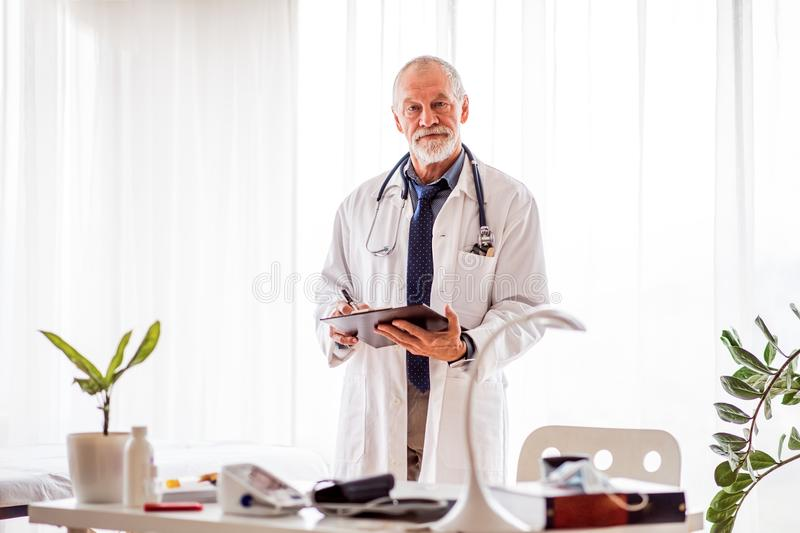 Senior doctor with smartwatch in office. Senior doctor in his office. Male doctor with smartwatch making notes stock image