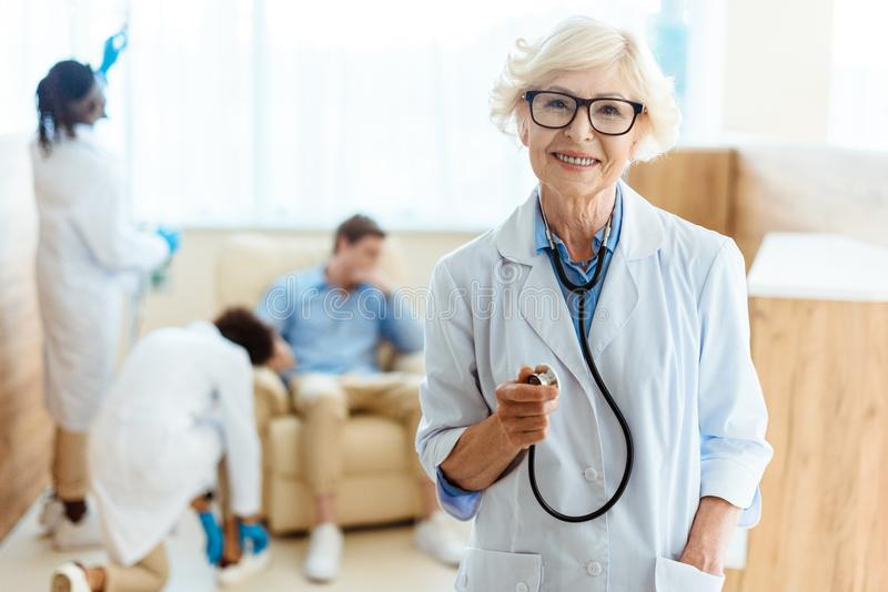 Senior doctor in lab coat and glasses smiling cheerfully and holding stethoscope. In hospital enviroment royalty free stock photos
