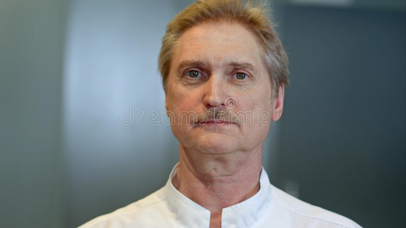 Senior doctor looking at camera. Close up. Professional shot in 4K resolution. 094. You can use it e.g. in your commercial video, business, presentation stock photo