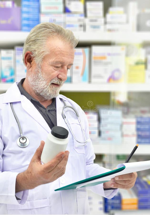 Senior doctor looking medicine bottle and patient chart on medicine shelves background. Pharmacist filling prescription in pharmacy drugstore royalty free stock image