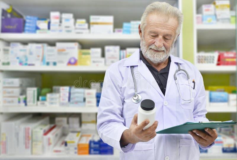Senior doctor looking medicine bottle and patient chart on medicine shelves background. Pharmacist filling prescription in pharmacy drugstore stock images