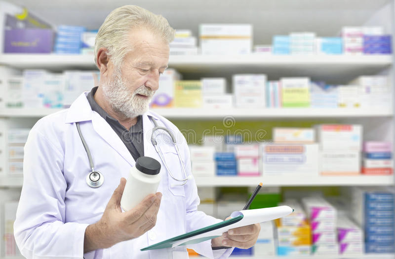 Senior doctor looking medicine bottle and patient chart on medicine shelves background. Pharmacist filling prescription in pharmacy drugstore stock photography