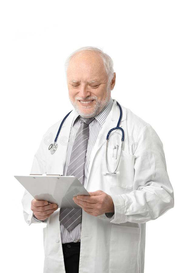 Senior doctor looking at papers smiling stock photo