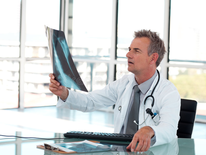 Senior doctor looking an X-ray royalty free stock image