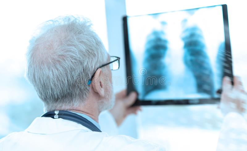 Senior doctor looking at x-ray; light effect. Senior doctor looking at x-ray in clinic; light effect stock images