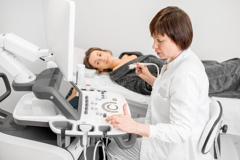 Doctor making ultrasound examination to a young woman. Senior doctor making an ultrasound examination to a young women patient royalty free stock image