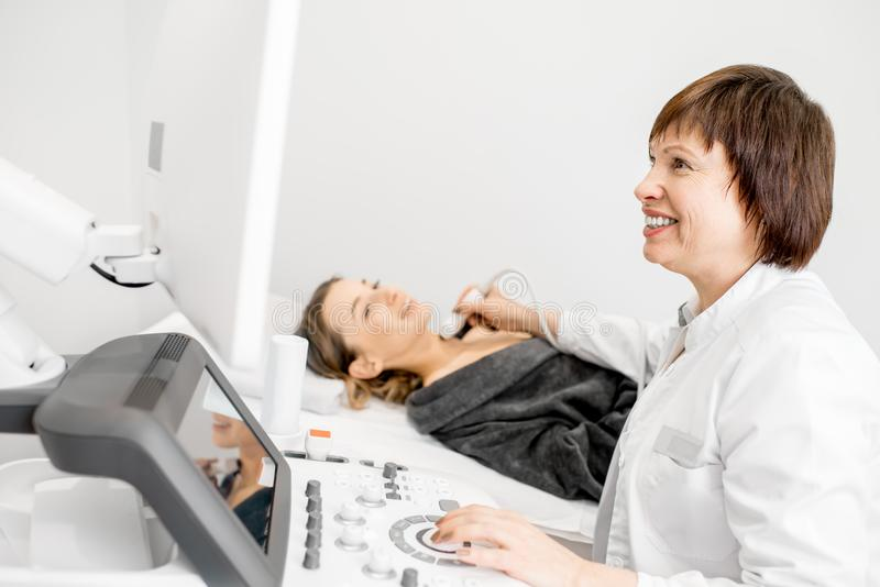 Doctor making ultrasound examination to a young woman. Senior doctor making an ultrasound examination to a young women patient royalty free stock photos