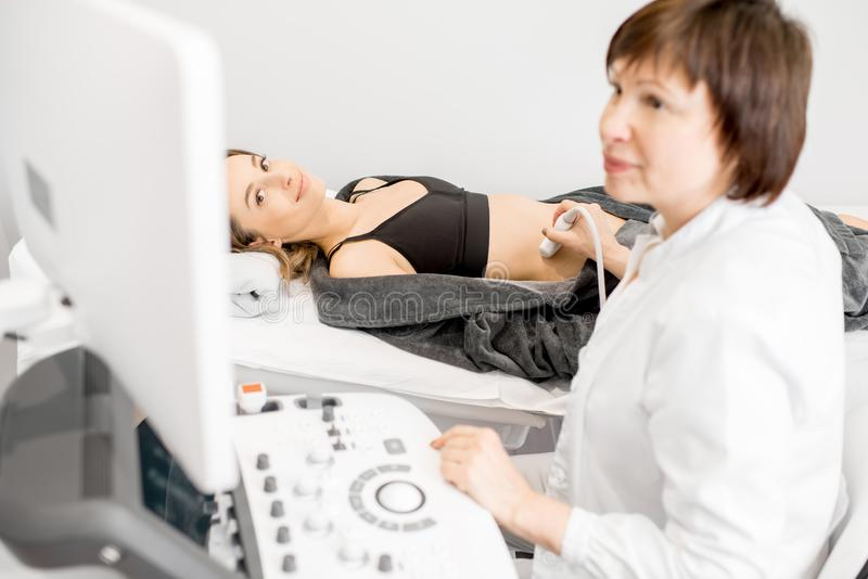 Doctor making ultrasound examination to a young woman. Senior doctor making an ultrasound examination to a young women patient royalty free stock photo
