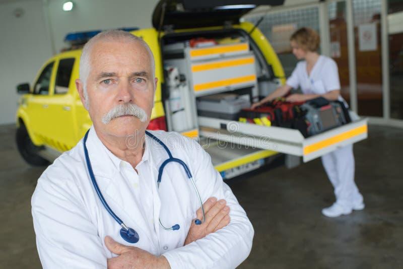 Senior doctor next to ambulance stock photos