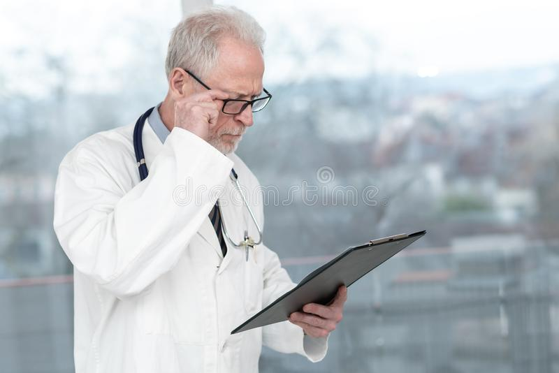 Senior doctor reading notes on clipboard royalty free stock photography