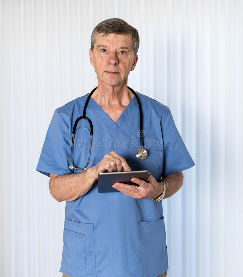 Senior doctor in scrubs facing camera. Senior male caucasian doctor with stethoscope in medical scrubs and checking notes on smartphone tablet device royalty free stock photos