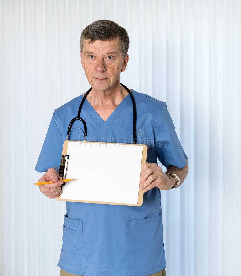 Senior doctor in scrubs facing camera. Senior male caucasian doctor with stethoscope in medical scrubs and confidently holding clipboard for message royalty free stock photos