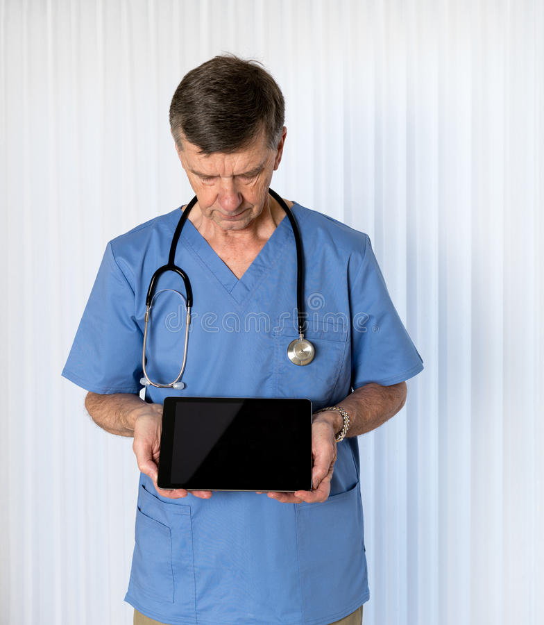 Senior doctor in scrubs facing camera. Senior male caucasian doctor with stethoscope in medical scrubs looking down and holding electronic tablet for message royalty free stock photos
