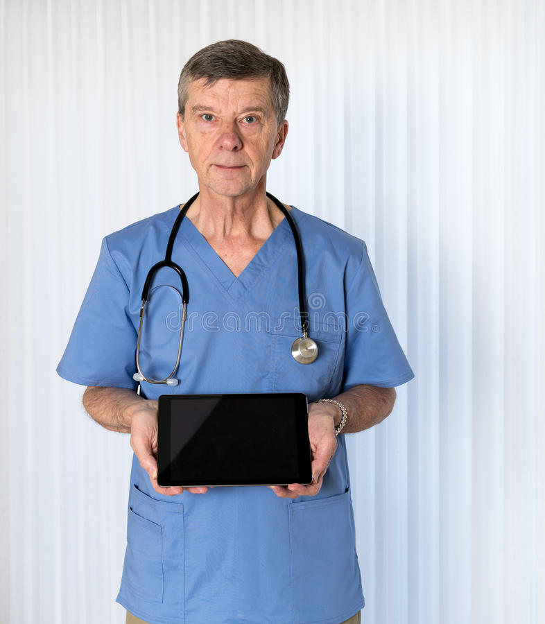 Senior doctor in scrubs facing camera. Senior male caucasian doctor with stethoscope in medical scrubs looking up and holding electronic tablet for message stock photo