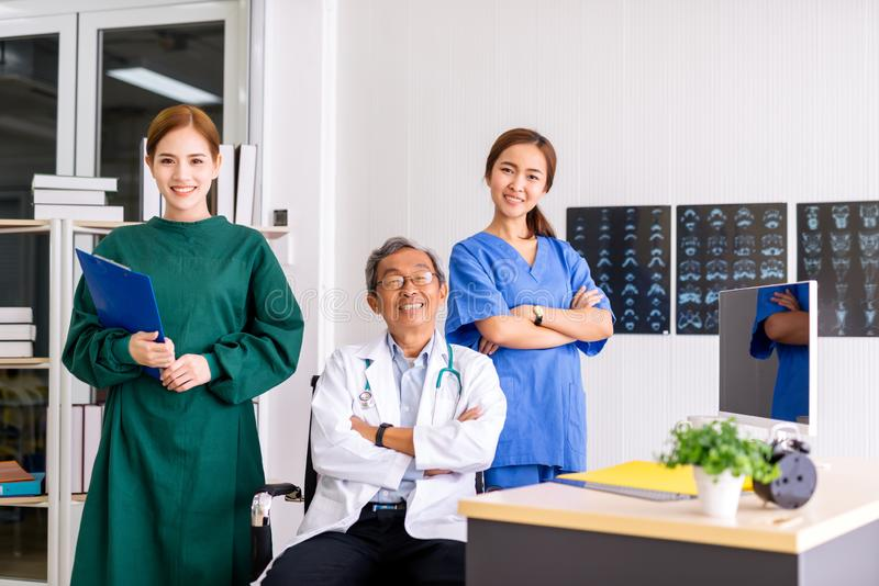 Senior Doctor sitting In Center Of Team with nurse and female doctor Surgeon portrait in office at hospital. royalty free stock images