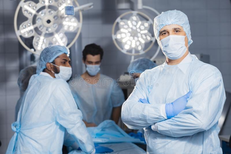Senior doctor, surgeon wearing medical protective mask in operating room stock photos