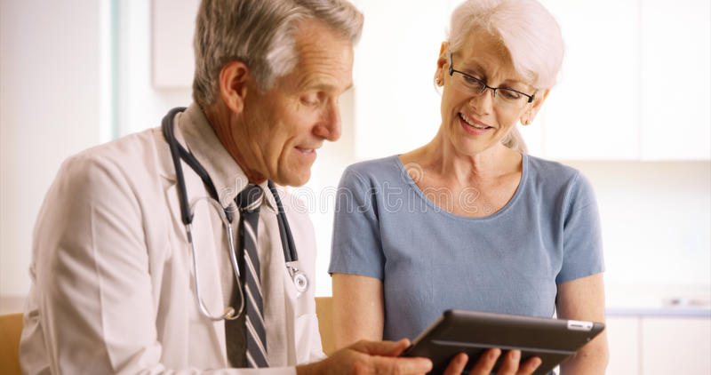 Senior doctor talking with elderly woman patient in the office with tablet stock image