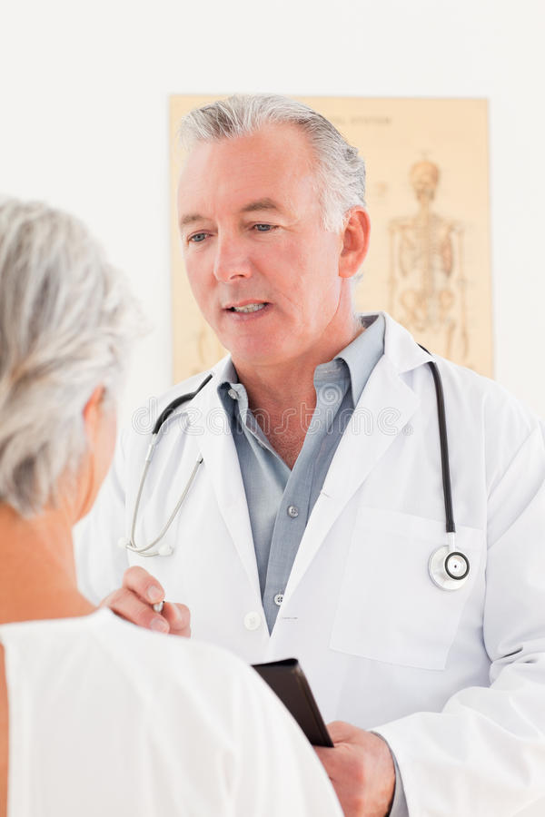 Senior doctor talking with his sick patient royalty free stock photography