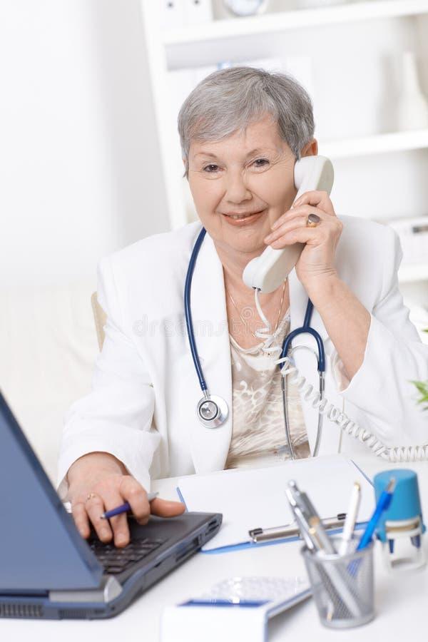 Senior doctor talking on phone stock photo