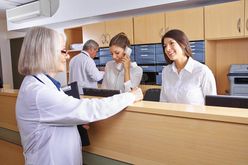 Senior doctor talking with receptionist. At hospital reception royalty free stock photography