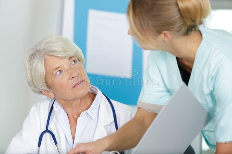 Senior doctor talking to nurse stock photos