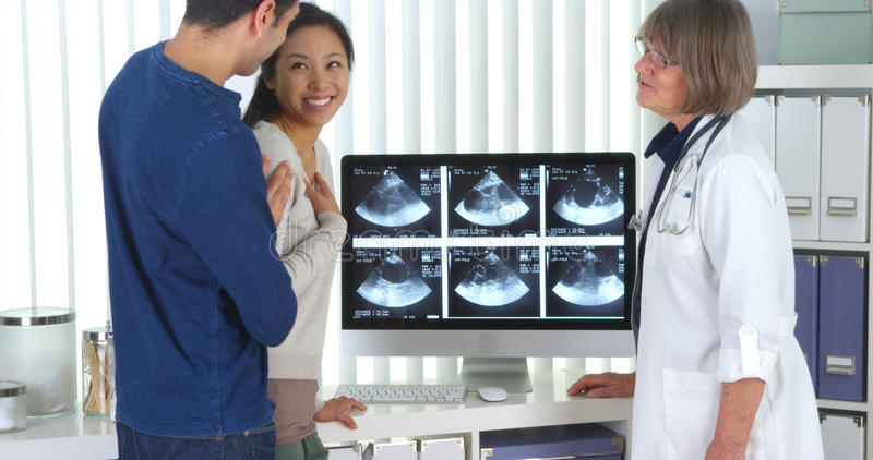 Senior doctor talks to interracial couple about pregnancy scans stock photography