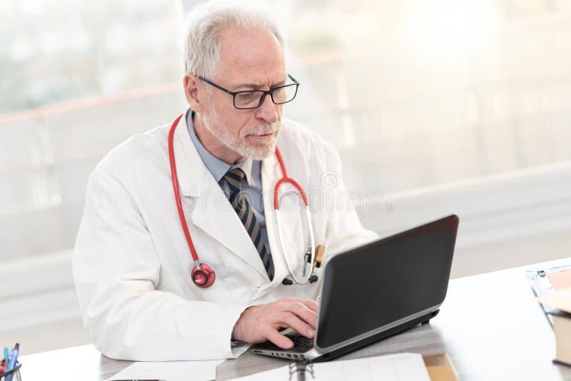 Senior doctor using laptop royalty free stock photography