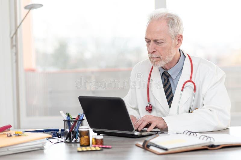 Senior doctor using laptop stock photo