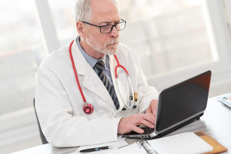 Senior doctor using laptop royalty free stock photo