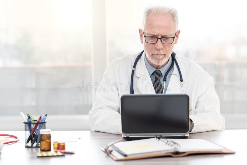 Senior doctor using laptop royalty free stock photos