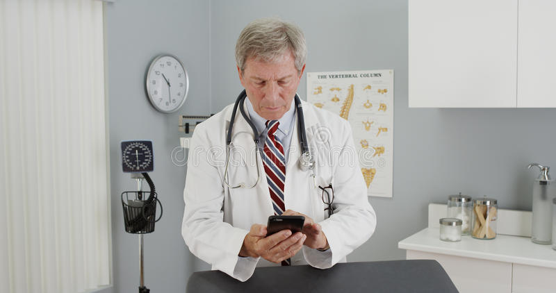 Senior doctor using smartphone in the office.  stock photo
